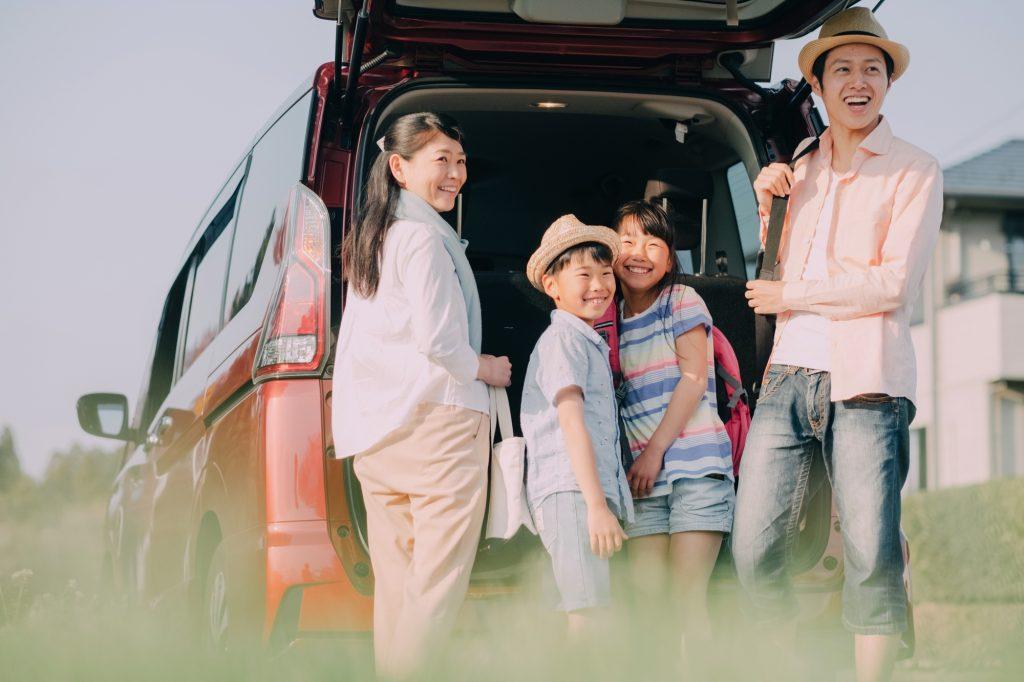 車のトランクを開けて笑顔で振り返る家族