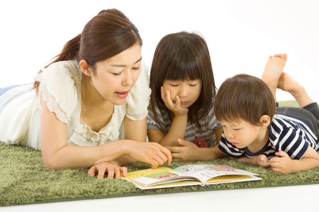 ママが子ども2人に絵本を読んでいる