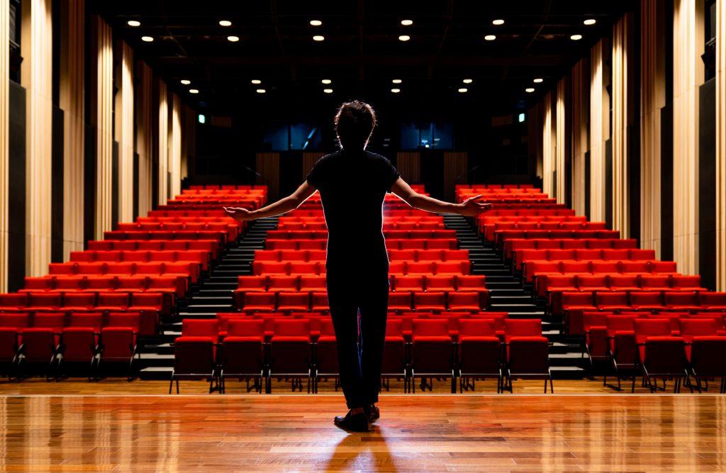 観客席に向かって手を広げる男性