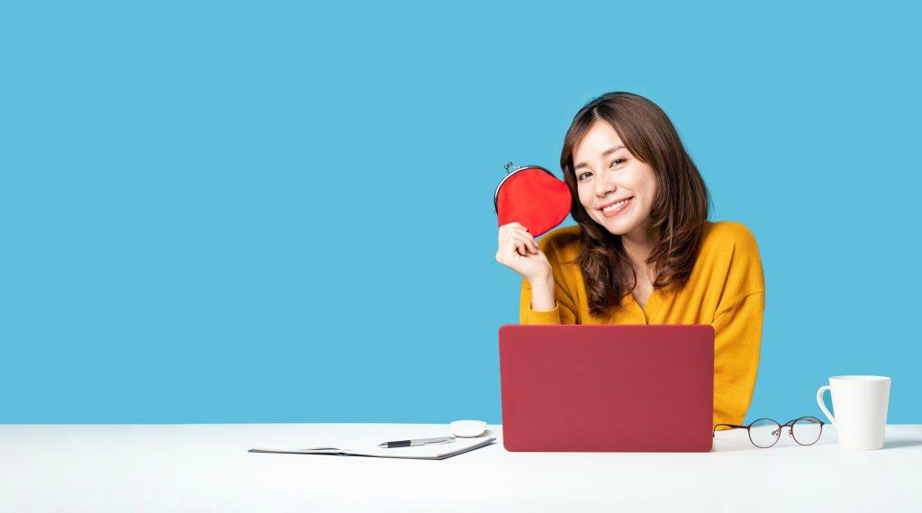 お財布を持った女性がパソコンの前に座っている