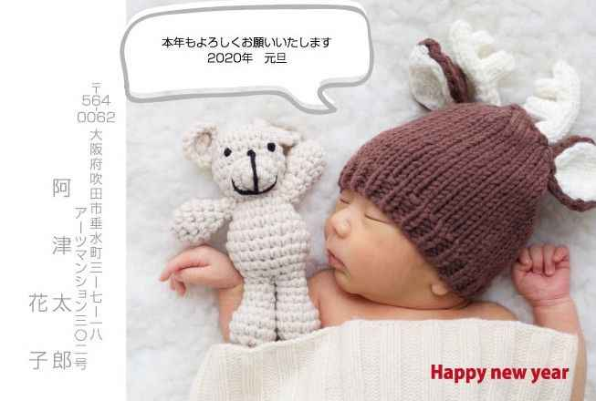 ニット帽をかぶった赤ちゃんが熊の人形の横で寝ている写真入り年賀状