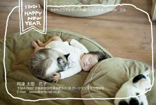 大きなクッションの上で猫にくっついて熟睡している赤ちゃんの写真入り年賀状