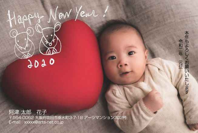 赤いハートのクッションの横で寝転ぶ赤ちゃんの写真入り年賀状