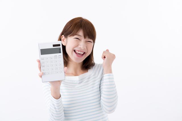 電卓を持った女性が笑顔でガッツポーズ