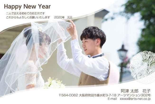 新郎が新婦のウエディングベールを上げている写真の年賀状