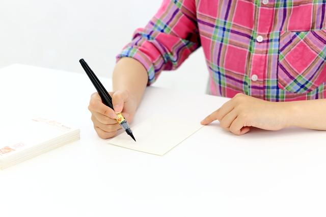 筆ペンで書く女性