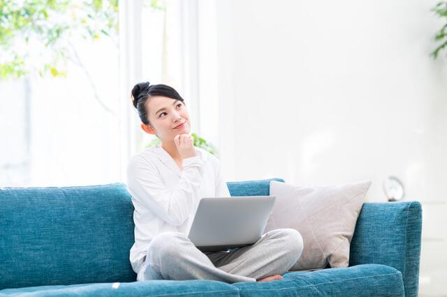 ソファーに座って考え事をする女性