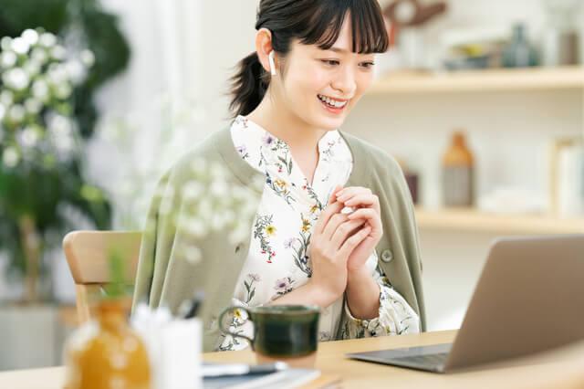机の前でパソコン画面を見ている女性
