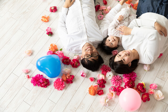 床に寝転がり笑顔を向ける家族