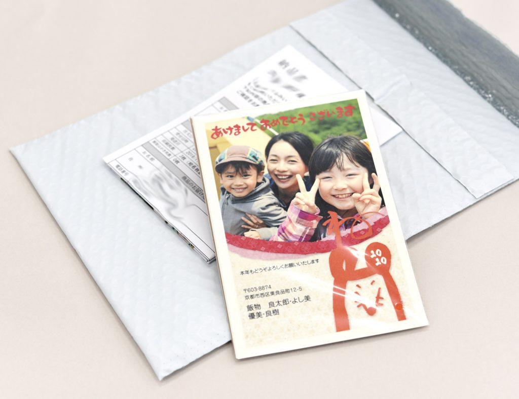 白い封筒の上に写真入り年賀状と納品書