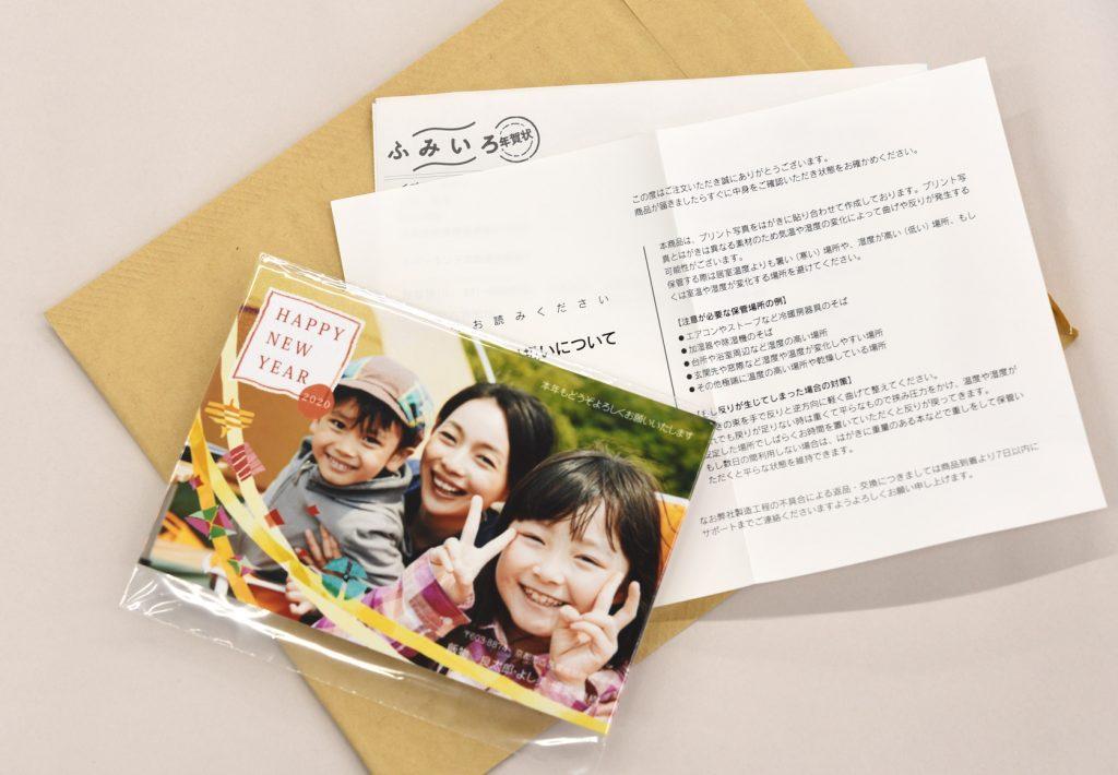 茶色の封筒の上に写真入り年賀状と納品書と「おはがきの取り扱いについて」の紙